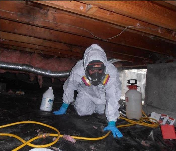Worker wearing protective gear and mask, crawling under a crawlspace